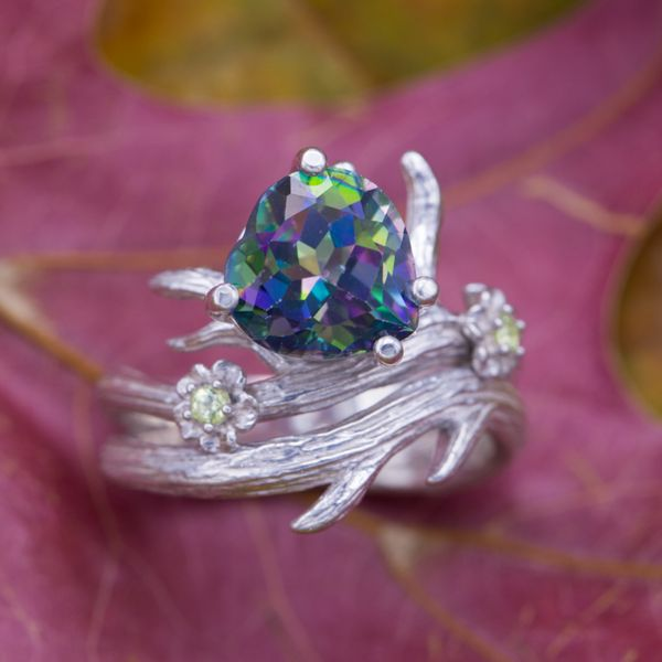 Mystic topaz is a unique, treated gem with a rainbow of colors reflecting from its facets. Here, a heart cut mystic topaz is the centerpiece for a bold, nature-inspired branch and flower ring with peridot accents.