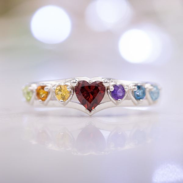 A deep red garnet center stone anchors a beautiful array of brightly-colored heart cut gemstones.