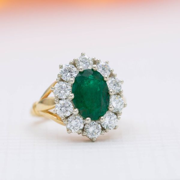A vintage-inspired emerald ring with a scalloped halo of chunky diamonds.