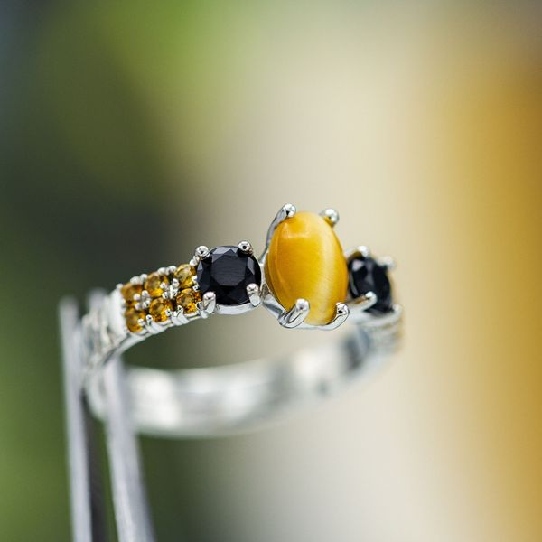 A honey-colored tiger's eye engagement ring with black onyx and citrine.