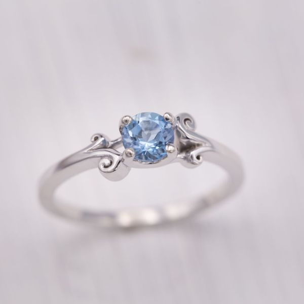 Curls of white gold crash like waves around the aquamarine center stone in this engagement ring.