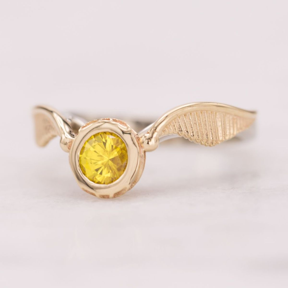 This snitch engagement ring sets a bright yellow sapphire as the center stone in the harry potter fans dream ring