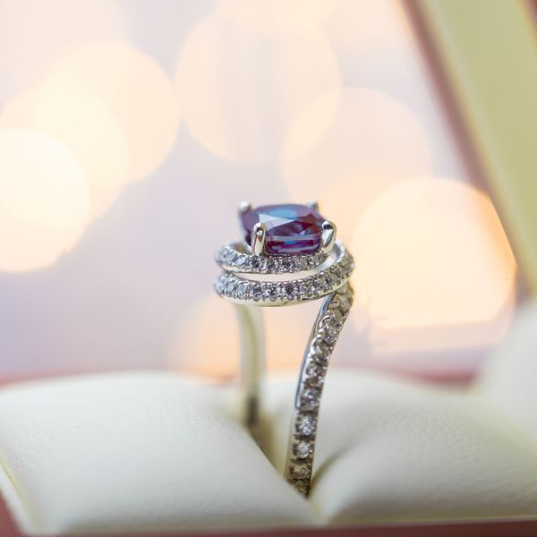 A spiral of diamonds creates a nest of sparkle for a beautiful alexandrite center stone.