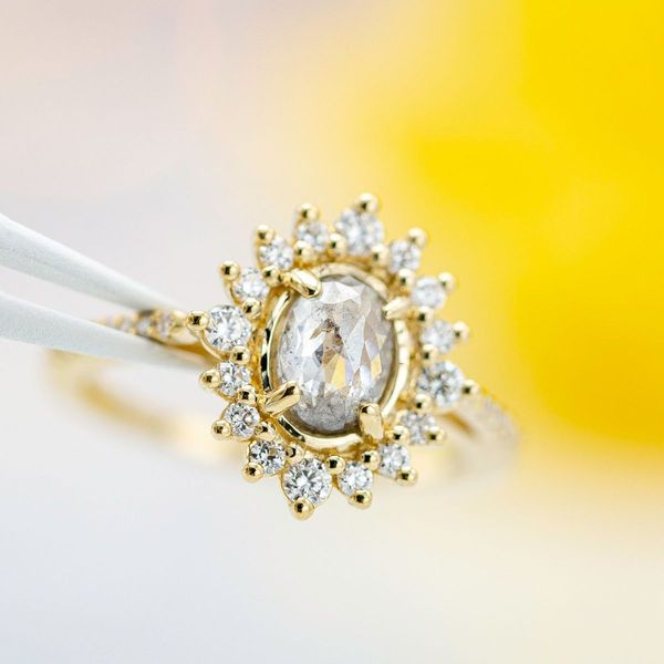 A gorgeous combination of a rose cut salt and pepper oval diamond and a sparkling sunburst halo. This ring's yellow gold brings a classic warmth to balance the cool, modern gray of the diamond.