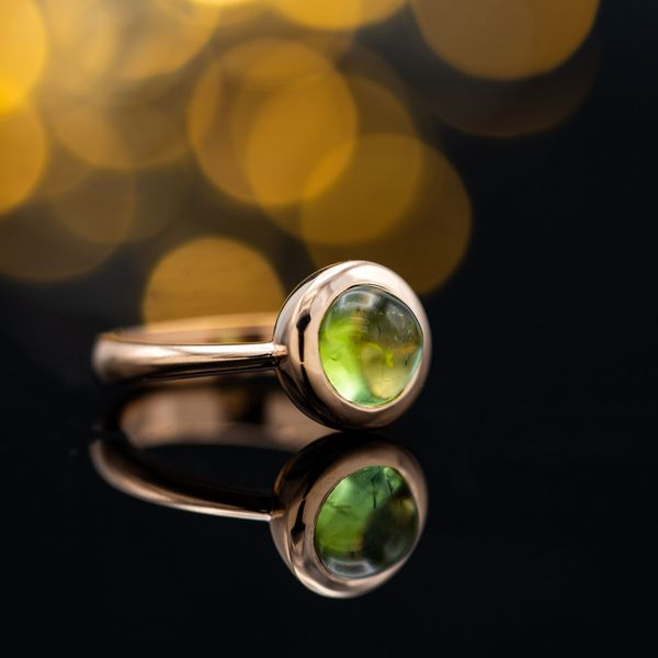 A sleek, modern design sets an apple green tourmaline cabochon in a rose gold bezel.