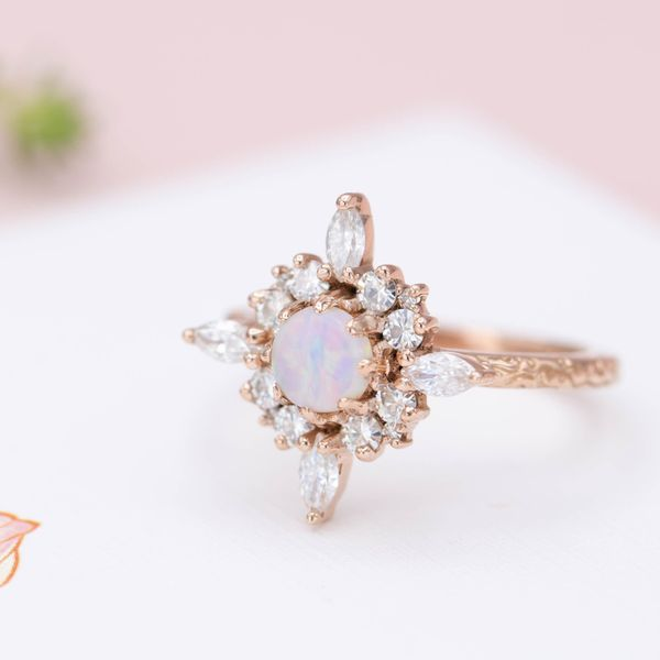 A unique halo extends like the star of Bethlehem around this ring's smaller opal center stone.