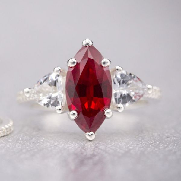 At once bold and delicate, pairing a large lab-created marquise ruby with trillion cut white sapphire and an thin, elegant pave band.