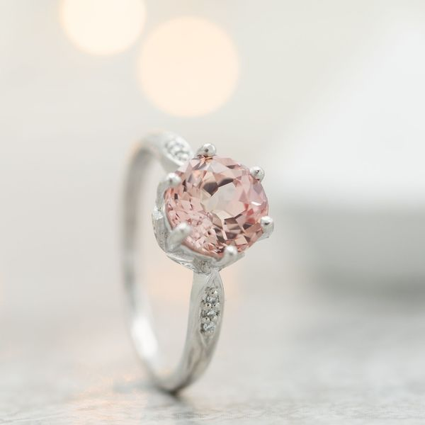 A delicate vintage-inspired engagement ring with a light, slightly peachy pink sapphire center stone.