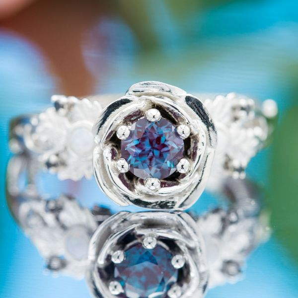 Round alexandrite nestled in the petals of this ring's rose setting, accented by white opal and black diamonds.