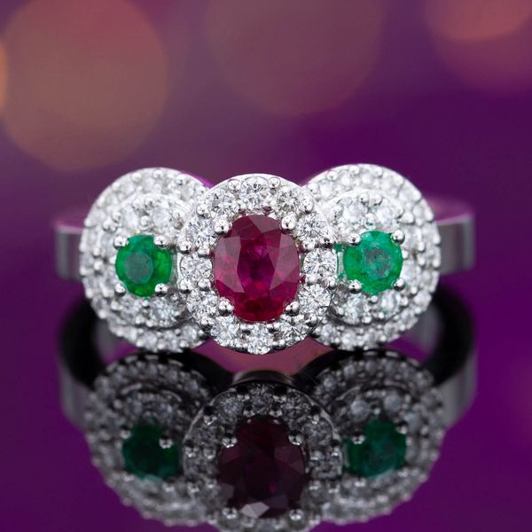 A unique play on a three-stone ring, surrounding the ruby and emeralds with diamond halos for a ton of sparkle.