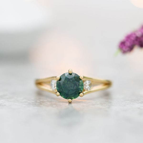 A deep green sapphire engagement ring with a delicate, modern split shank and diamond side stones.