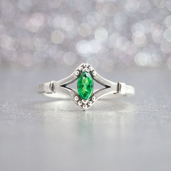 A marquise-cut emerald center stone in this ring pairs beautifully with the antiqued, riveted white metal setting around it.
