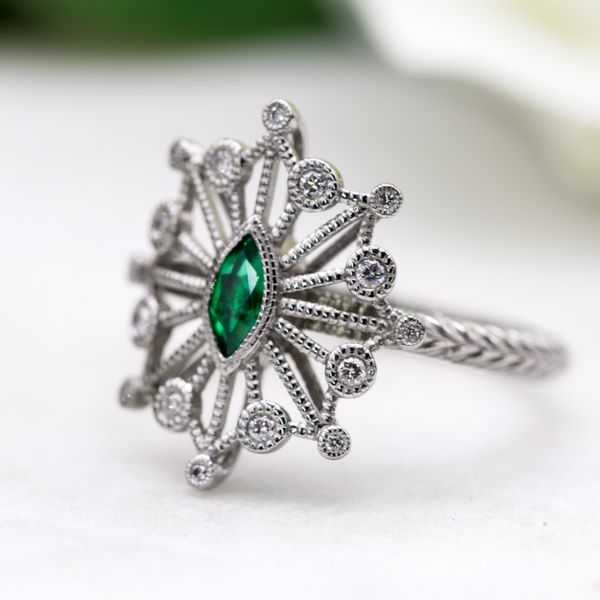 A gorgeous, Art Deco-inspired ring design is open and airy and nods toward the elongated navette ring shape. Like a diamond-laced snowflake with a marquise emerald center.