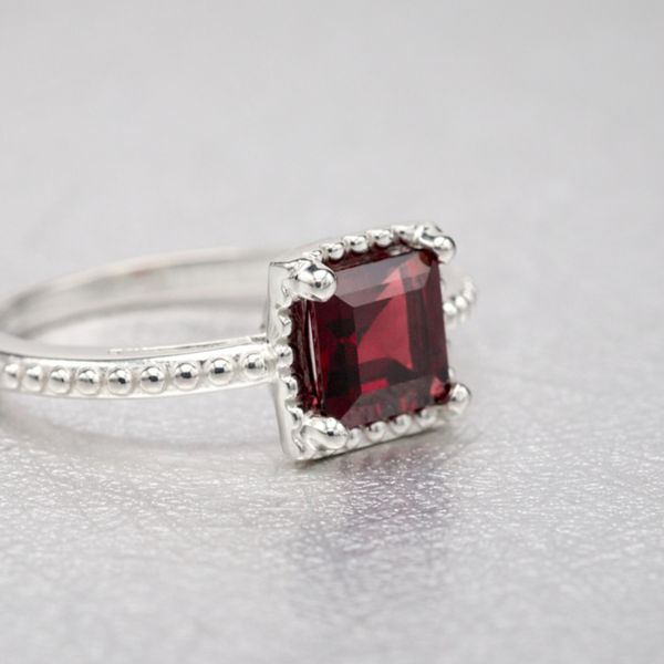 A play on the typical pave and halo ring, this garnet ring skips the diamonds in favor of elegant, polished beadwork.