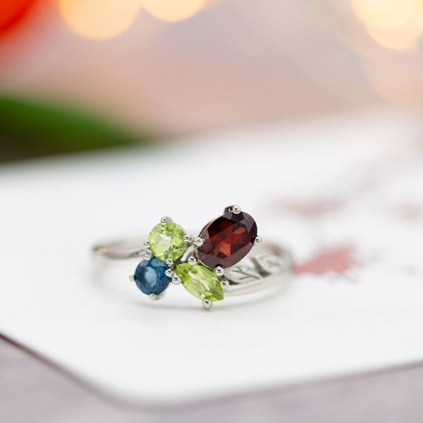 A modern asymmetrical cluster ring with red garnet, peridot and topaz.