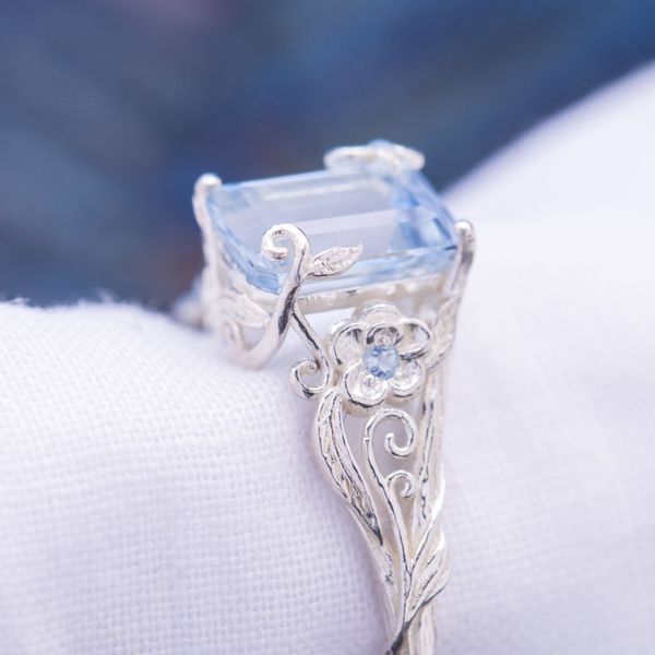 The aquamarine in this delicate, leafy ring is held in place by bits of vining that seem to grow up and over the center stone.