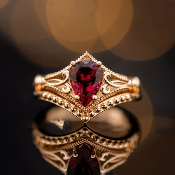 A breathtaking, vintage-inspired bridal set in rose gold features a uniquely deep red tourmaline.