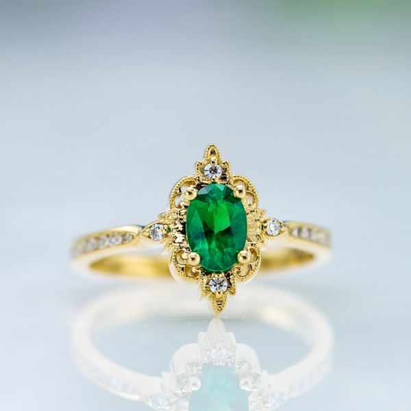 An oval emerald pairs with an intricate gold halo in the perfect vintage-inspired engagement ring.